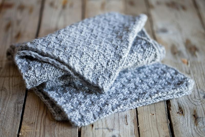 Knitted grey scarf. On wooden background royalty free stock photography