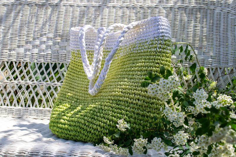 Knitted hand-made green-white bag stays on white  wicker couch in the garden with blooming spirea bouqet aside. Knitted hand-made green-white bag stays on white royalty free stock photos