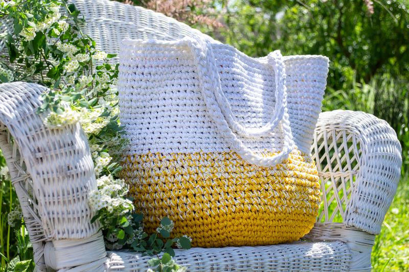 Knitted hand-made yellow-white bag stays on white  wicker chair with blooming spirea bouqet aside on blurry garden background. Knitted hand-made yellow-white bag stock photos