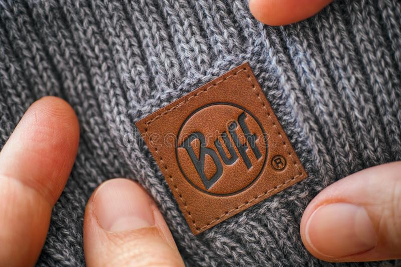 Knitted hat with clothes label Buff in woman hands royalty free stock photos