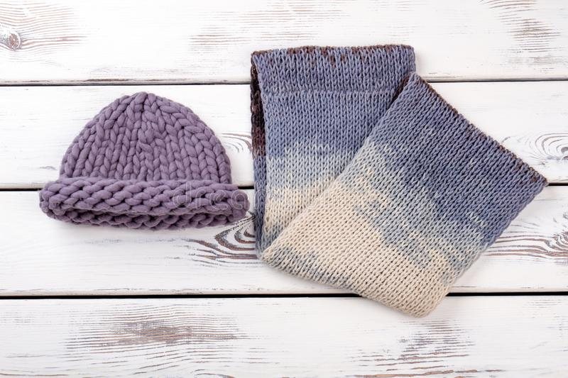 Knitted hat and scarf. White wooden desks surface background royalty free stock photo