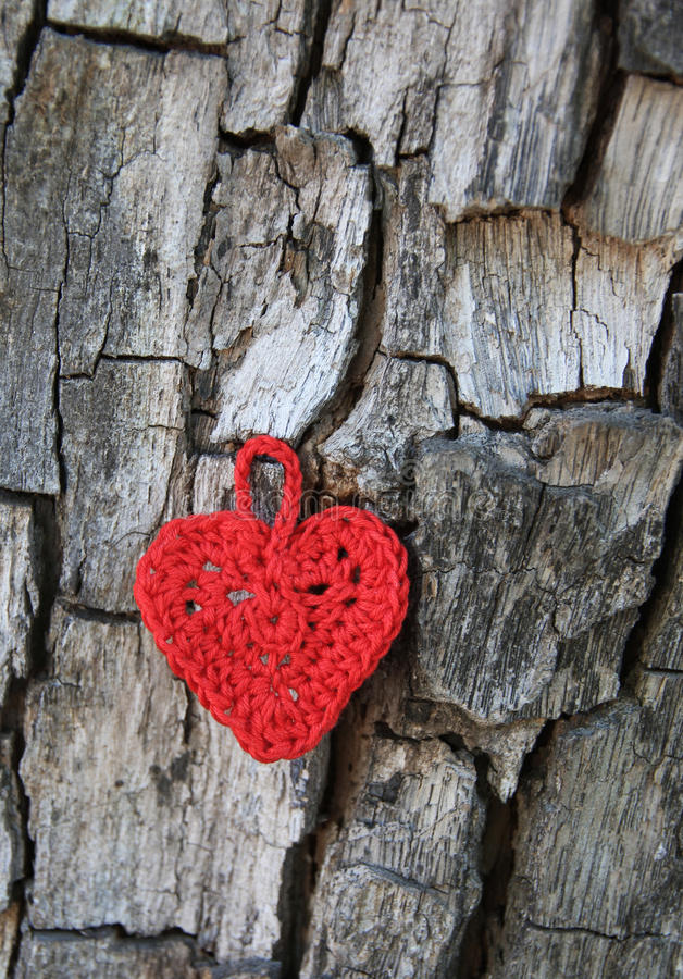 Knitted heart on bark cracks. Love treats. Heart as Love symbol. Handwork, knitting by a hook stock photos