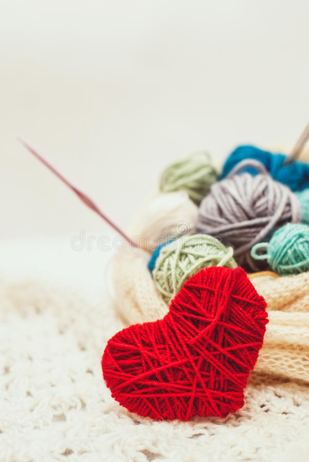Knitted heart symbol and balls of yarn royalty free stock photography