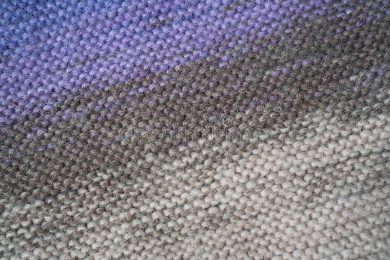 Knitted horizontal textured multicolored fabric on a white background. Fragment of a brown, purple, beige color sweater. Texture, stock photography