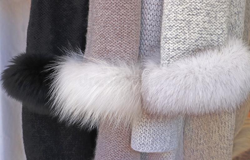Knitted jackets with faux fur. Sleeves of knitted jackets with faux fur hanging in a store stock photography