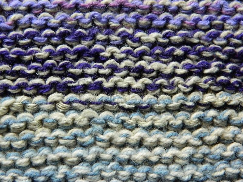 Knitted knitting with knitting needles. garter stitch. Multicolored stock image