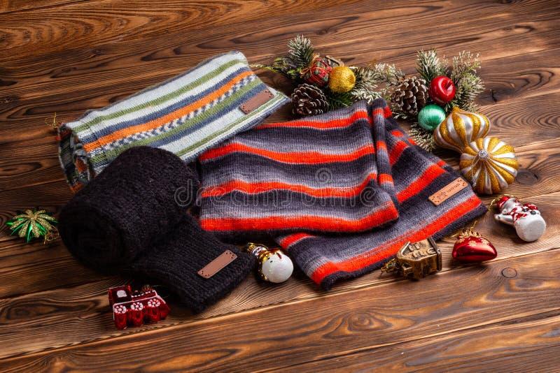 Knitted listrou scarves listrados, as luvas feitas malha pretas e os brinquedos do Natal no fundo de madeira imagens de stock