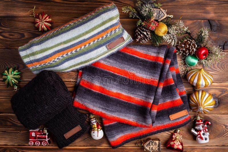 Knitted listrou scarves listrados, as luvas feitas malha pretas e os brinquedos do Natal no fundo de madeira foto de stock royalty free