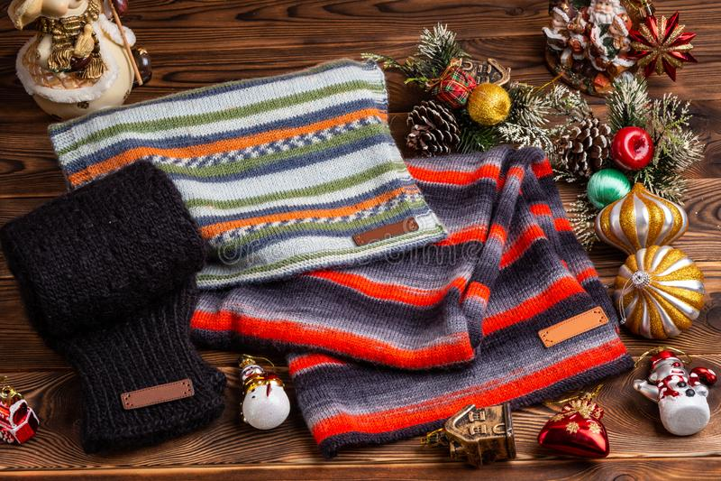 Knitted listrou scarves listrados, as luvas feitas malha pretas e os brinquedos do Natal no fundo de madeira imagem de stock royalty free