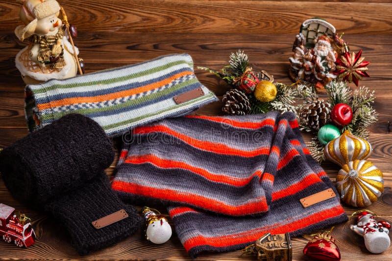 Knitted listrou scarves listrados, as luvas feitas malha pretas e os brinquedos do Natal no fundo de madeira imagens de stock royalty free