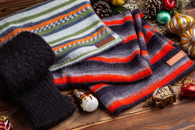 Knitted listrou scarves listrados, as luvas feitas malha pretas e os brinquedos do Natal no fundo de madeira fotos de stock royalty free