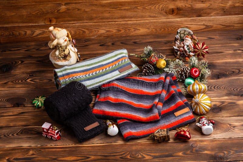 Knitted listrou scarves listrados, as luvas feitas malha pretas e os brinquedos do Natal no fundo de madeira imagem de stock