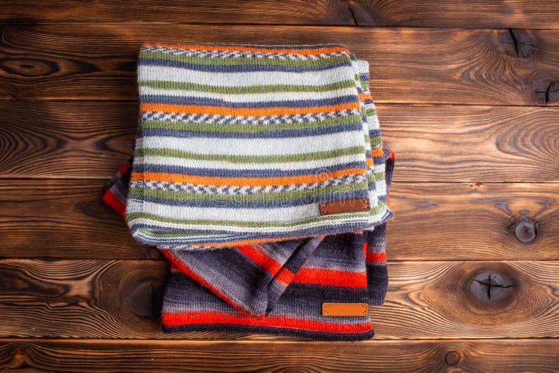 Knitted listrou scarves no fundo de madeira marrom imagem de stock royalty free