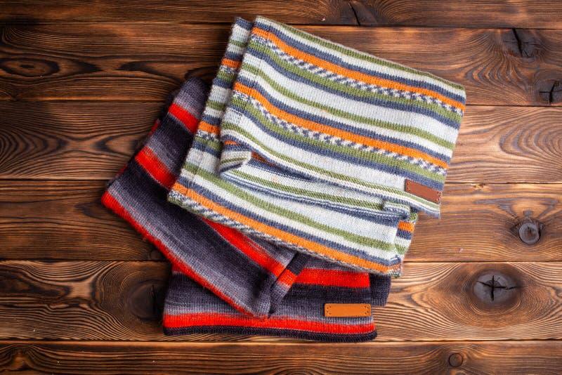Knitted listrou scarves no fundo de madeira marrom imagens de stock