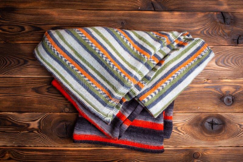 Knitted listrou scarves no fundo de madeira marrom imagens de stock royalty free