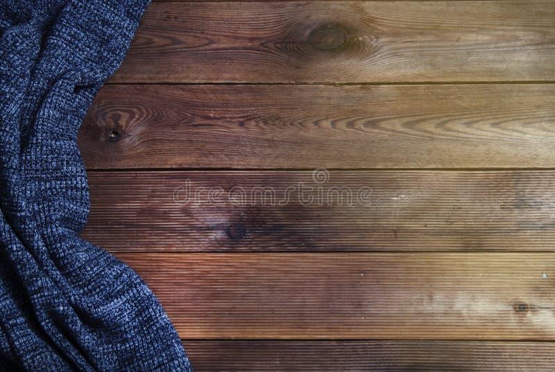 Knitted morna textured a obscuridade - cobertura cinzenta em um fundo de madeira Vista superior, espaço para o texto Fundo do out imagem de stock royalty free