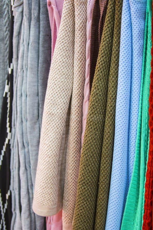 Knitted multi-coloriu mantas, coberturas, texturas feitas malha da tela na loja foto de stock royalty free