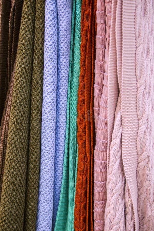 Knitted multi-coloriu mantas, coberturas, texturas feitas malha da tela na loja imagem de stock