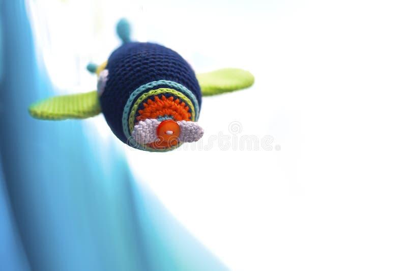Knitted multi-coloriu o avião em um fundo azul e branco imagem de stock royalty free