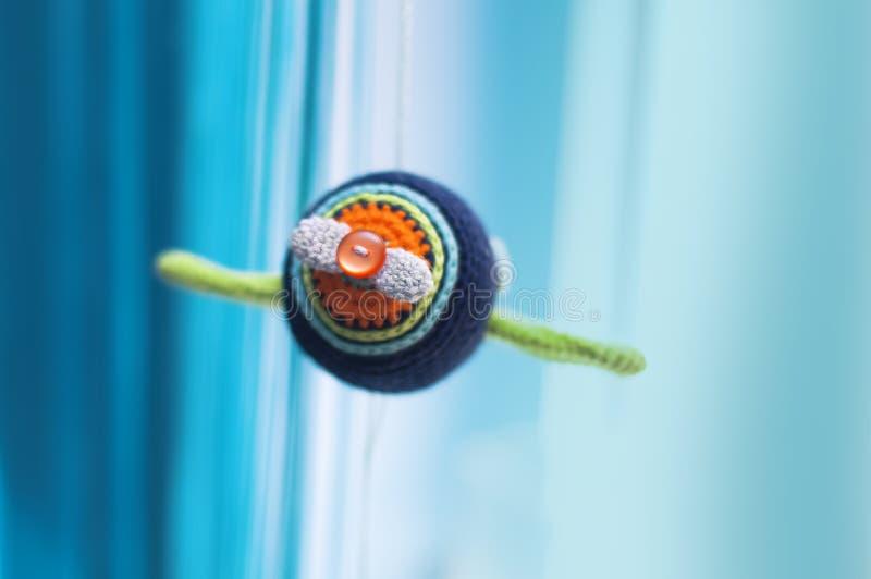 Knitted multi-coloriu o avião em um fundo azul e branco imagem de stock