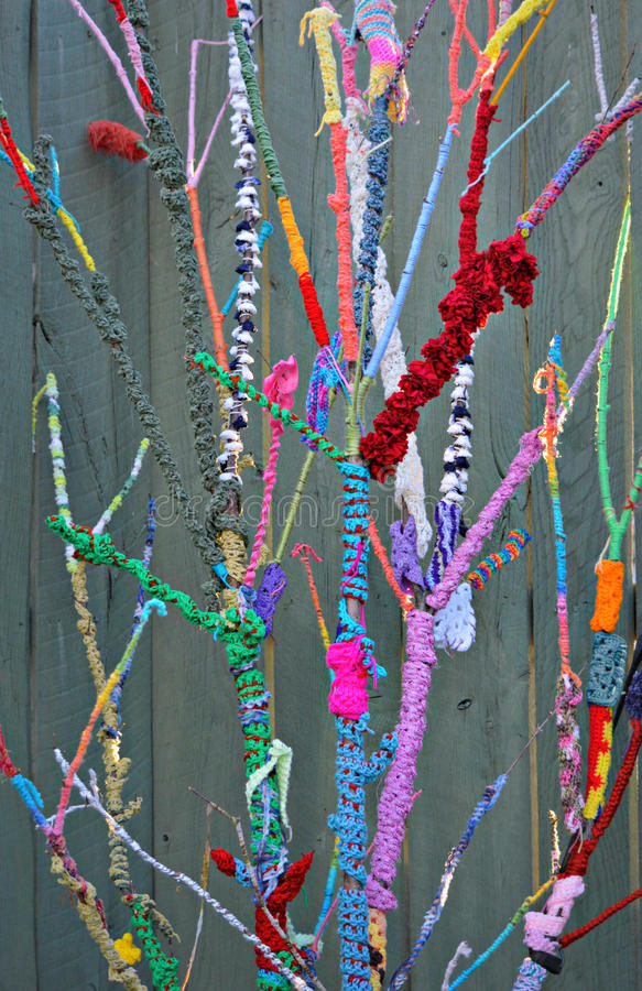 Knitted Nature. Colorful strands of yarn knitted and wrapped around the branches of a young tree outdoors against a wooden fence. This display of knitted nature stock image