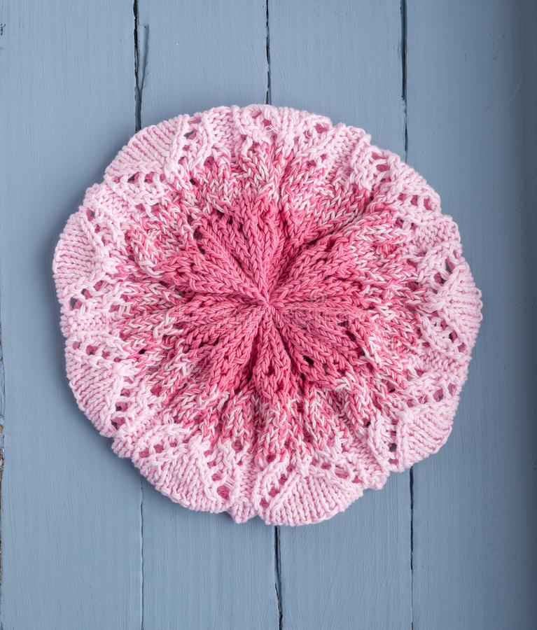 Knitted openwork pink beret for women on a blue background. stock photography