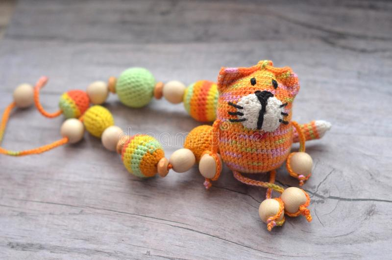 Knitted pink striped handmade crafted cat. Children`s toy. Crochet pattern. Handicraft manufacturing. royalty free stock image