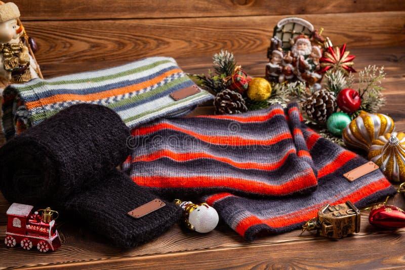 Knitted rayó las bufandas rayadas, las mangas hechas punto negras y los juguetes de la Navidad en fondo de madera fotografía de archivo libre de regalías