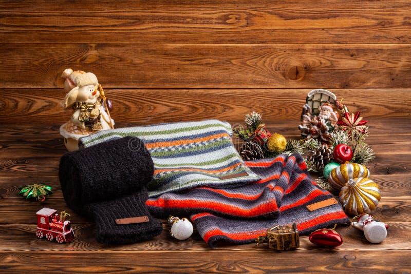 Knitted ray? las bufandas rayadas, las mangas hechas punto negras y los juguetes de la Navidad en fondo de madera fotografía de archivo libre de regalías