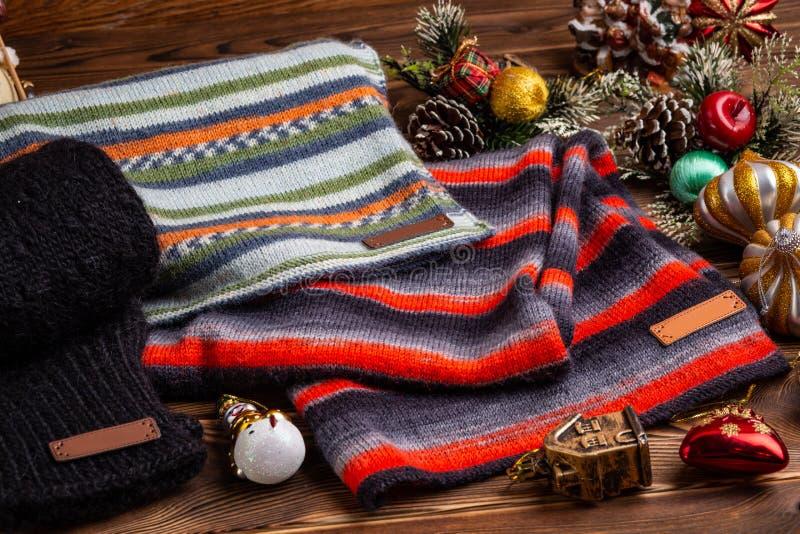Knitted ray? las bufandas rayadas, las mangas hechas punto negras y los juguetes de la Navidad en fondo de madera foto de archivo libre de regalías