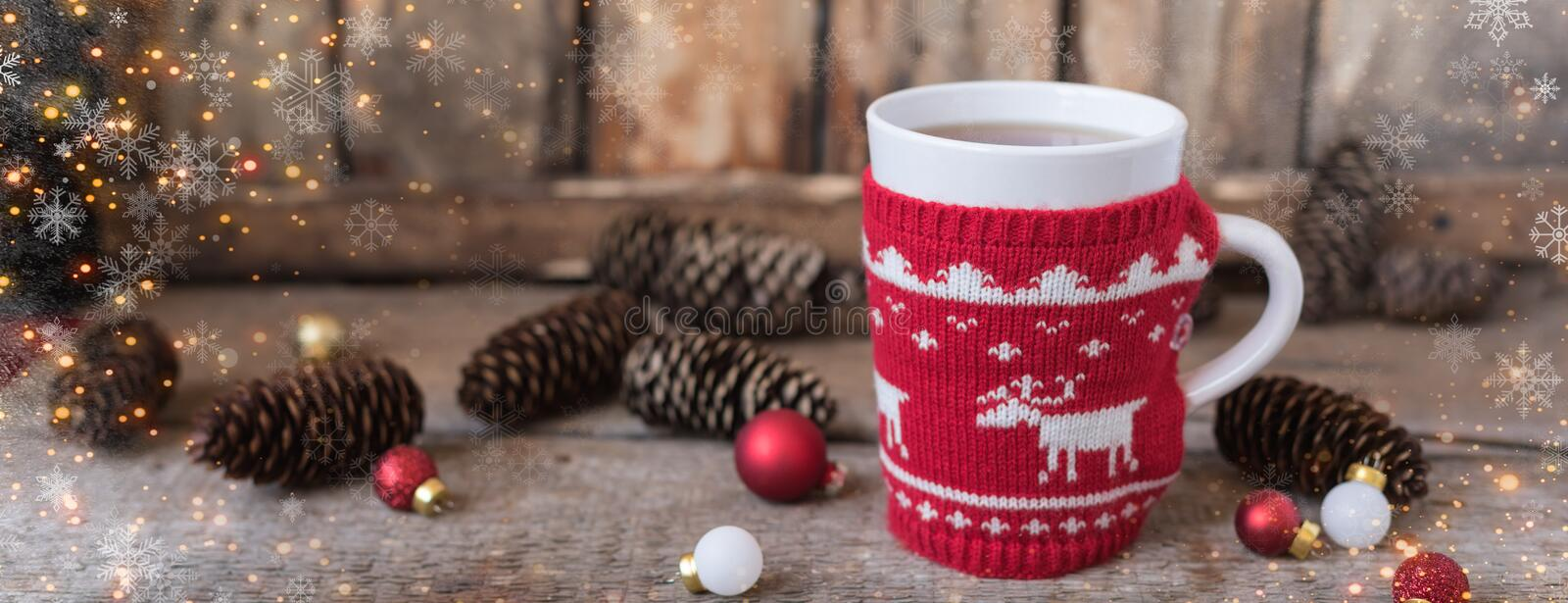 Knitted red cup with white reindeer, christmas lights with cones and toys at rustic background, banner. Knitted red cup with white reindeer, christmas lights royalty free stock photo