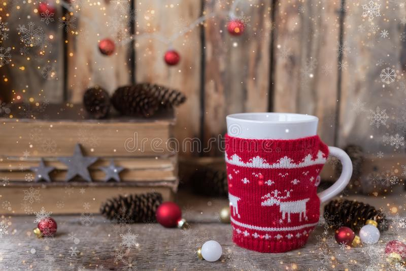 Knitted red cup with white reindeer, christmas lights with old books, cones and toys at background. Postcard concept royalty free stock photos
