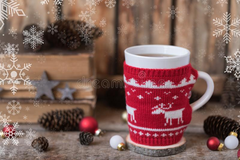 Knitted red cup with white reindeer, christmas lights with old books, cones and toys at background? snowflakes texture. Knitted red cup with white reindeer royalty free stock photography