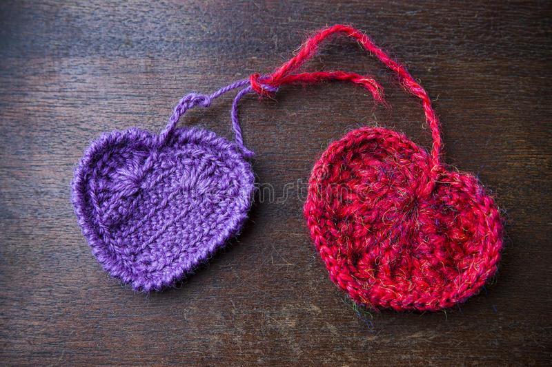 Knitted red and purple hearts on a wood background stock photography
