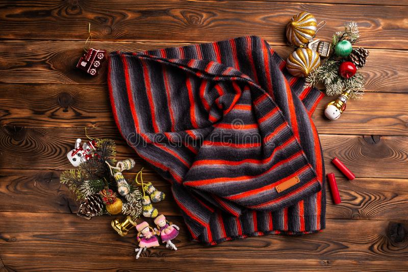 Knitted scarf in black, red and white stripes and christmas decorations on a wooden background royalty free stock photography