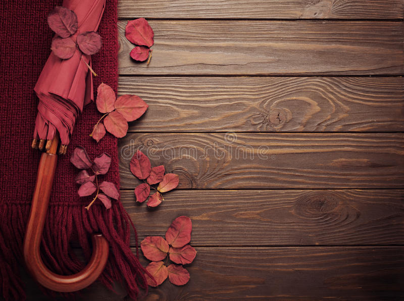 Knitted scarf of burgundy color with autumn leaves and an umbrella on a dark wooden background. Top view. Flat lay stock photos