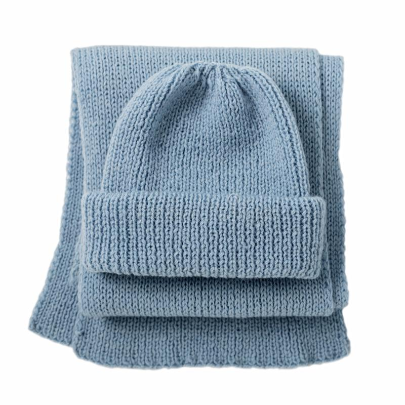 Knitted scarf and cap of blue color on isolated white background royalty free stock photo