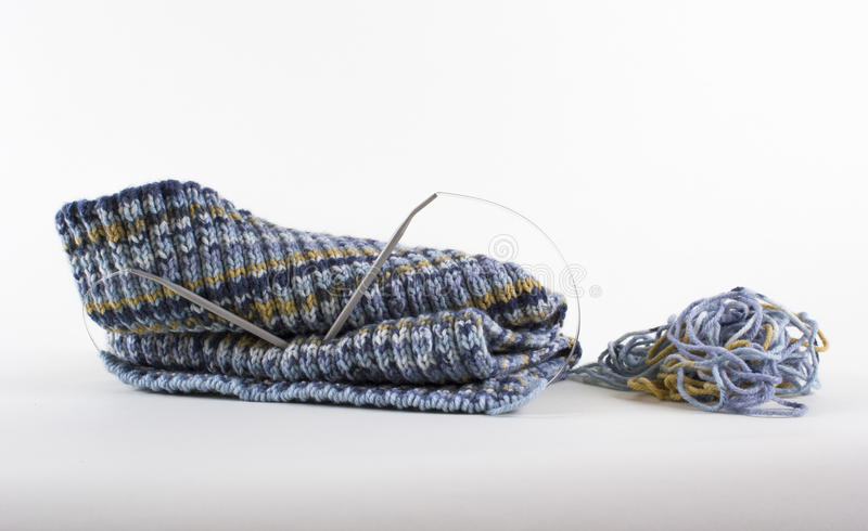 Knitted scarf made of woolen thread. Knitting on knitting needles with woolen thread, Autumn Plaid for the baby, Knitting on knitting needles, Warm woolen plaid royalty free stock photo