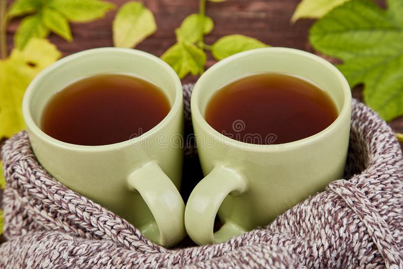 Knitted scarf with warm cup of tea. Knitted scarf with two warm cups of tea, autumn leaves on wooden table. Autumn. Fall season. Still life royalty free stock photo