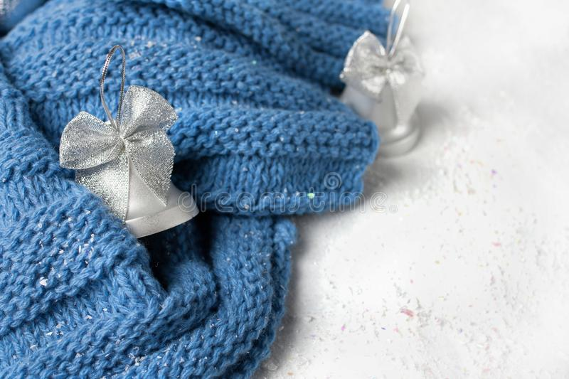 Knitted scarf. Winter concept. Blue white color . A cup of hot tea flavored with a knitted scarf and little hat on white backgroung. Cold color stock photography