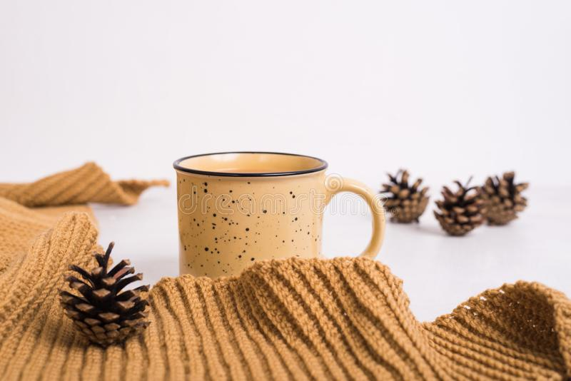 Knitted shawl, cup of coffee and cones on white background royalty free stock images