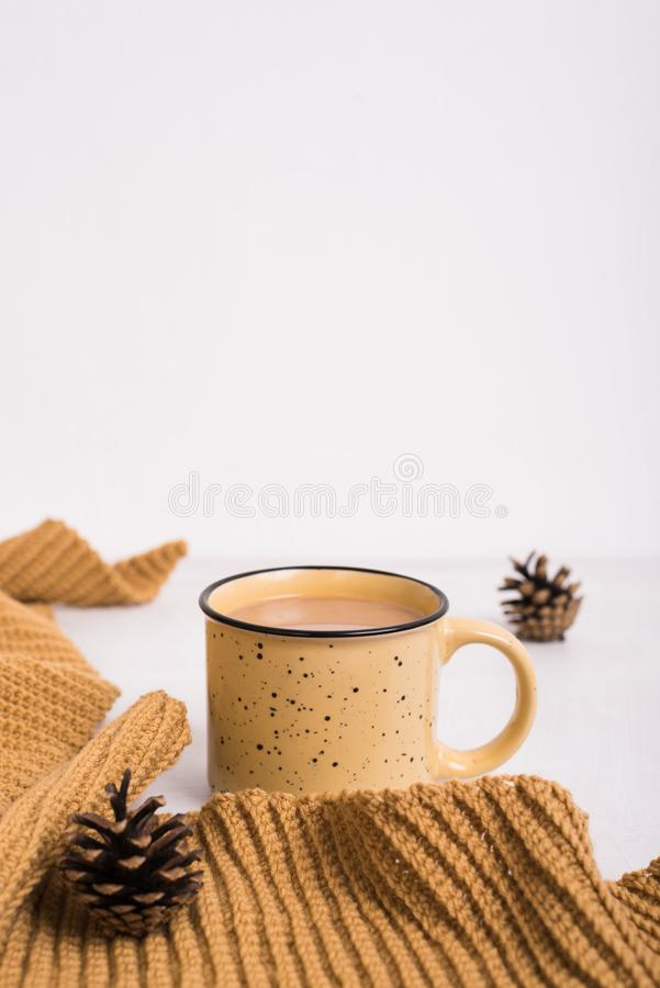 Knitted shawl, cup of coffee and cones on white background stock photo