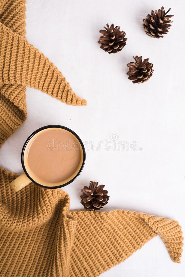 Knitted shawl, cup of coffee and cones on white background stock photos