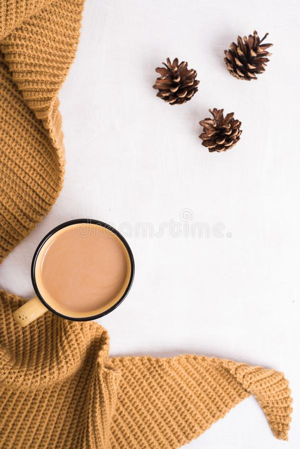 Knitted shawl, cup of coffee and cones on white background royalty free stock image