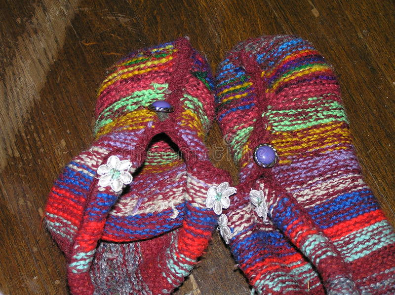 Knitted slippers. Knitted baby slippers product of multi-colored woolen threads stock photography