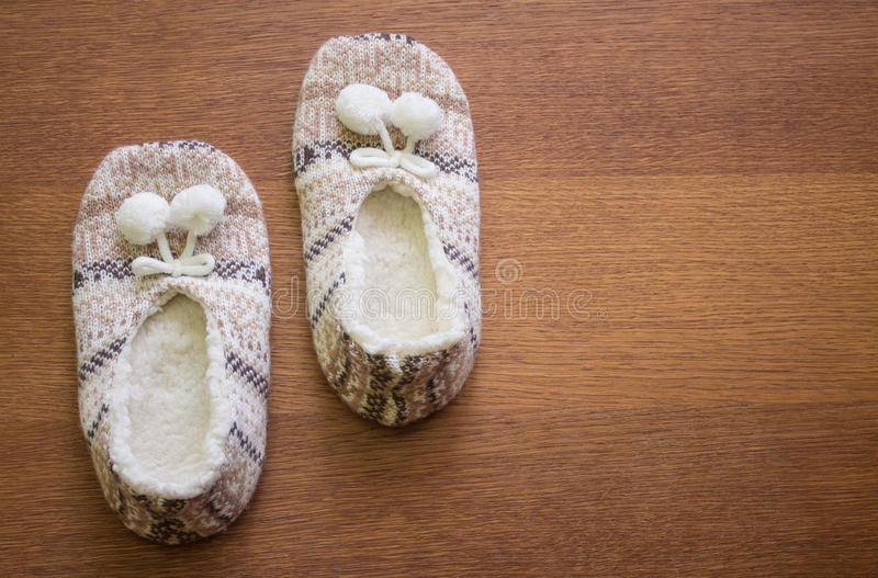 Knitted slippers with pompoms. On wood floor stock photo