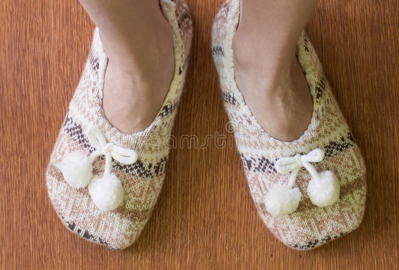 Knitted slippers with pompoms. On wood floor stock photos