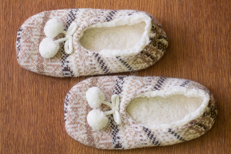 Knitted slippers with pompoms. On wood floor stock image