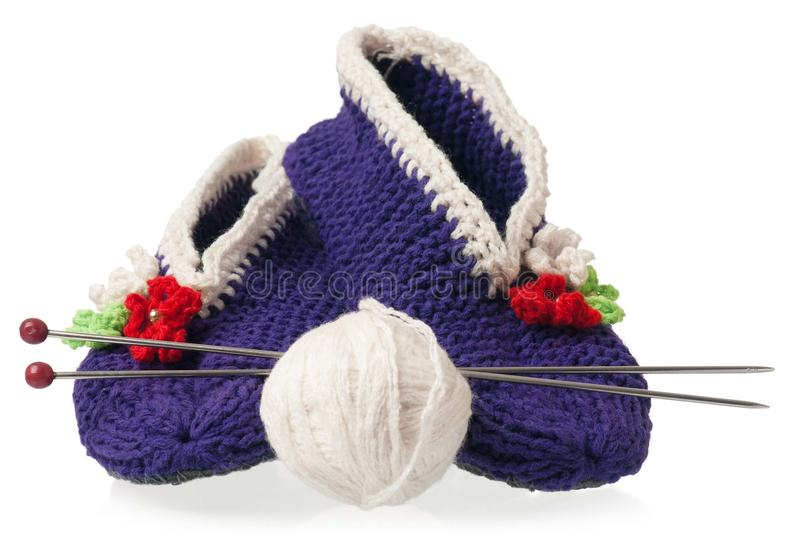Knitted slippers. Knitted warm slippers with yarn threads isolated on white background stock photography