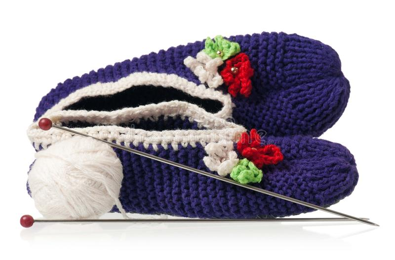 Knitted slippers. Knitted warm slippers with yarn threads isolated on white background royalty free stock photos
